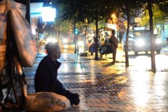 Người đàn ông thao thức nhìn trời mưa, bên cạnh là những bọc ve chai đã lặn lội nhặt cả ngày trời.
