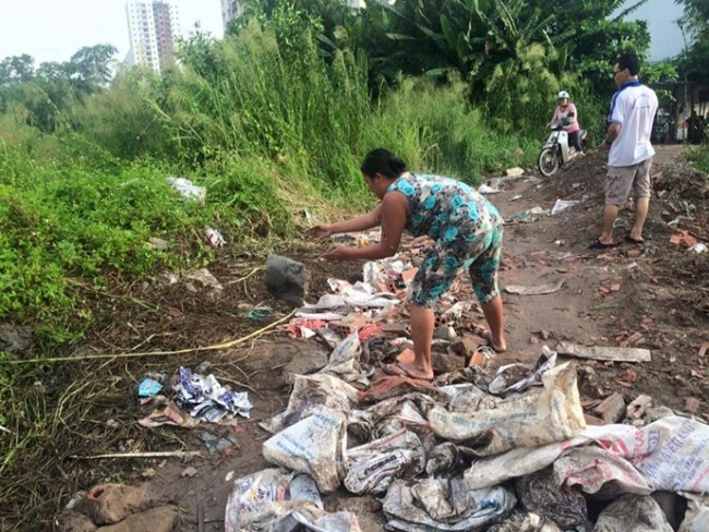 Chị Loan dọn dẹp phụ mẹ bớt đống xà bần cho người đi đường dễ lưu thông - Ảnh: Bùi Thư