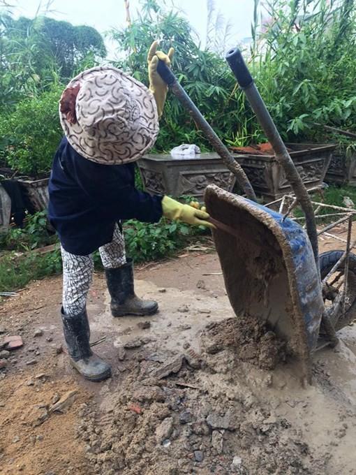 Một chị thợ hồ gần đó phải đổ đất vào những đoạn đường thủng để mặt đất được bằng phẳng - Ảnh: Bùi Thư
