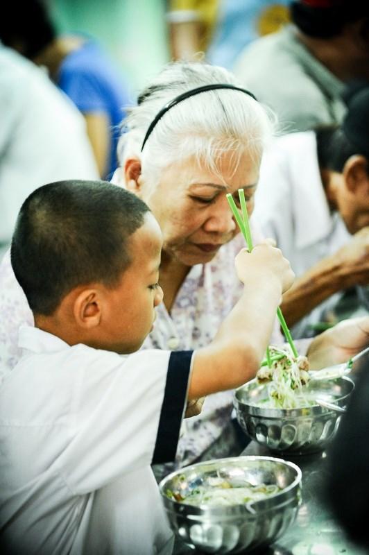 Người bà nhường phần thịt cho đứa cháu nhỏ - Ảnh: Nguyên Trương