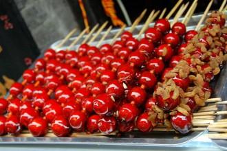 những cái kẹo hồ lô gồm trái cây bọc đường ghim vào một que tre mà tôi từng mê tít
