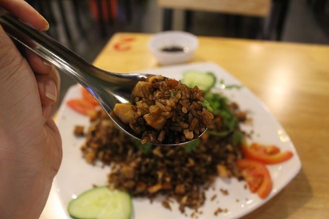Điểm nhấn của món ăn chính là những hạt cơm chiên màu đen săn chắc, thịt xá xíu thơm lừng, cảm giác giòn tan của những hạt cơm rang (màu trắng) vui miệng.
