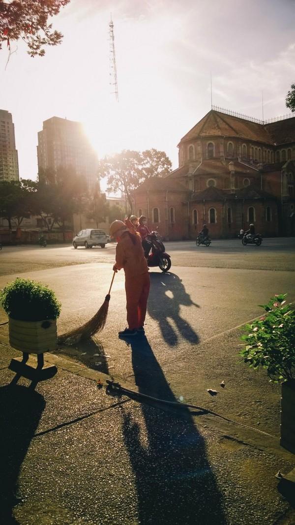 Cô dọn vệ sinh đường phố trong nắng sớm