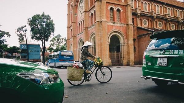 Cô đạp xe bán bánh tét