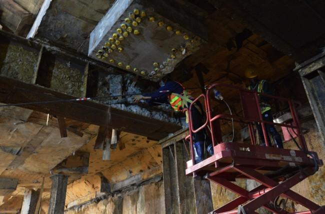 Những mảng bê tông còn dính lại trên các trụ sắt được công nhân dùng máy khoan loại bỏ để chuẩn bị dỡ sàn