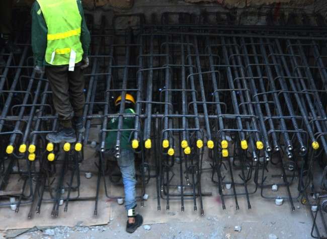 Công nhân nam dùng sức mạnh uốn các thanh sắt dày nặng