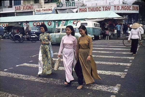 Những người phụ nữ mặc áo dài thong thả trên đường phố Sài Gòn.