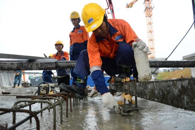 Bê tông bơm vào khuôn, công nhân dùng 4 đầm dùi để bê tông được nèn chặt lại