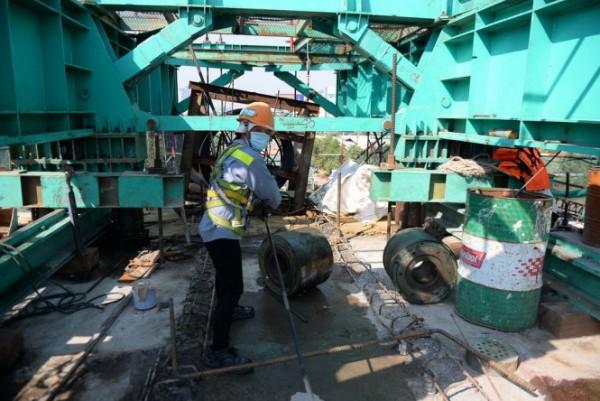 Công nhân thi công trên nhịp dầm đầu tiên của cầu Metro Sài Gòn. Ảnh: Hữu Khoa