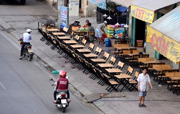 Đầu giờ chiều các quán nhậu trên đường Phạm Văn Đồng bắt đầu bày bàn ghế ra tận sát bờ đường để chuẩn bị bán cho khách vào buổi tối - Ảnh: Duyên Phan.