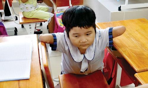 """Sau khi cẩn thận xếp hết sách vở vào hộc bàn, Thương tự dùng đôi tay """"cánh cụt"""" của mình để đu vào ghế ngồi."""