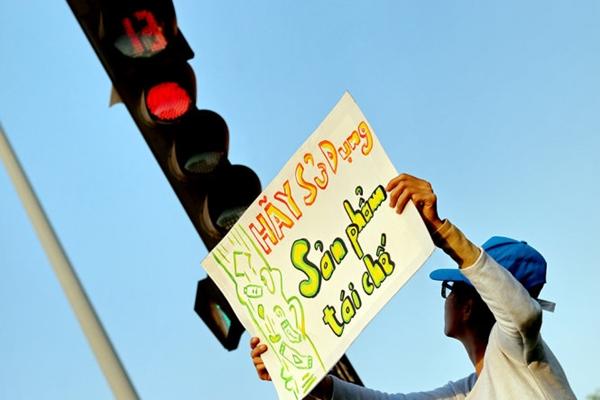 Khi đèn đỏ, người đi đường dừng xe, các sinh viên lại xuống đường giơ các thông điệp - Ảnh: Ngọc Hiển