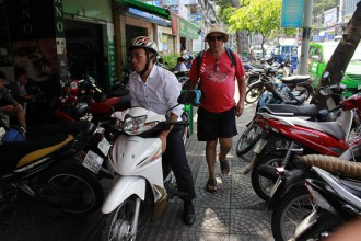 Một du khách nước ngoài di chuyển khó khăn trên đường Nguyễn Thị Minh Khai (quận 1) vì vỉa hè bị chiếm dụng.