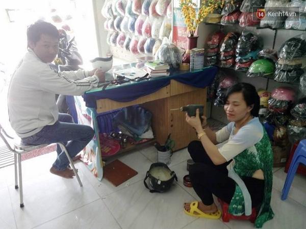 Nữ giám đốc trẻ rất vui và hào hứng khi có cơ hội tự tay sửa nón cho các chú xe ôm.