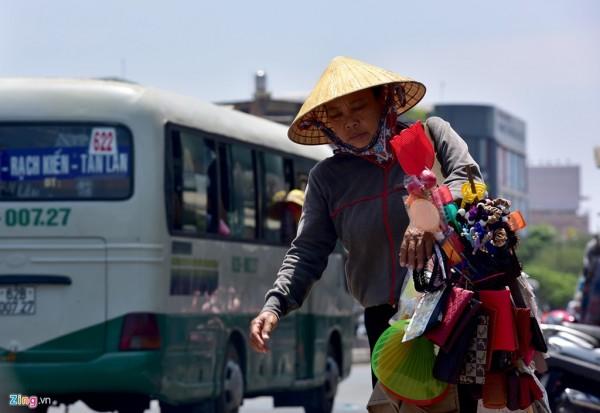 """Bà Hà Thị Tần (bán đồ dạo) sau khi ăn trưa tiếp tục rảo bước trên đường Hồng Bàng (quận 11) dưới cái nắng dội xuống. """"Làm nghề này không thể ngồi một chỗ chờ người đến mua. Dù trời đang nắng như thế này, nhưng không ra đường không bán được hàng, tiền đâu mà sống"""", người phụ nữ quê Bình Thuận chia sẻ."""