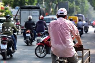 Trên đường 3/2 (quận 10), mồ hôi ướt đẫm áo người đàn ông đạp chiếc xe ba gác thu mua đồ cũ.