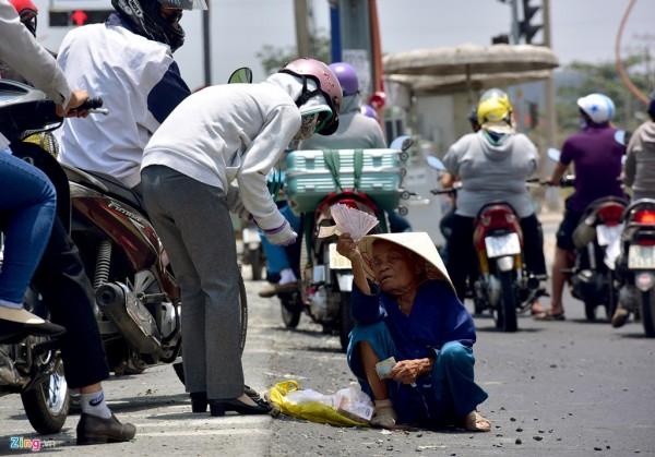 Bên Xa lộ Hà Nội (quận 9), trên đầu nắng dội, dưới mặt đường nhựa bốc hơi nóng hừng hực, bà cụ này vẫn ngồi bán vé số cho khách dừng đèn đỏ.