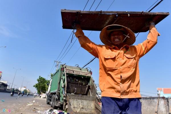 14h30, ông Nguyễn Thanh Sơn (quận 12) đóng tấm cửa xe kết thúc chuyến thu gom và giao rác tại điểm tập kết trên quốc lộ 1, quận 12 sau những giờ làm việc giữa nắng.