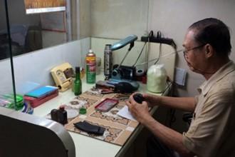 Ông Nguyễn Văn Tần cặm cụi trong góc nhỏ tiệm ảnh mà mình xin ngồi nhờ.