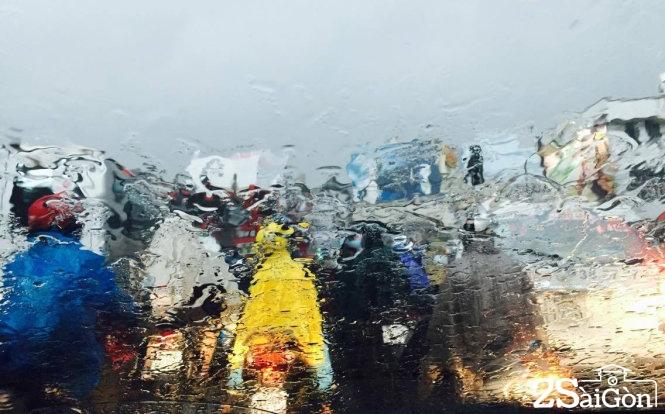 Dòng người trong mưa tại ngã tư Phú Nhuận. Ảnh: C.TH.