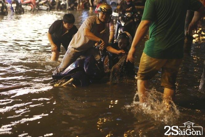 Một cụ già té ngã trên đường Hoa Phượng, Q.Phú Nhuận được người dân dìu vào lề đường. Ảnh: GIA TIẾN