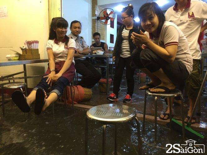 Nước ngập tấn công hàng quán ở đường Phan Xích Long. Ảnh: CHẾ THÂN