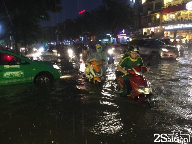 Nước ngập hơn nửa bánh taxi, xe máy tại giao lộ Hoa Phượng - Phan Xích Long (Phú Nhuận). Ảnh: CHẾ THÂN