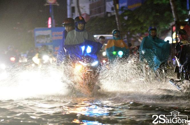 Xe cộ chạy trên đường Trường Sơn (Q.Tân Bình) đầy nước, Ảnh: Hữu Thuận