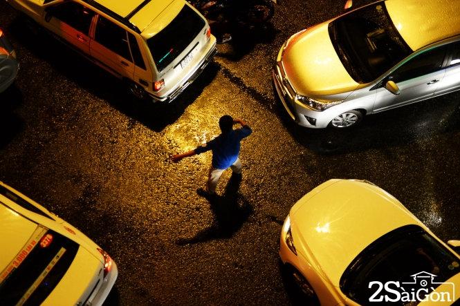 """Một thanh niên """"tả xung hữu đột"""" điều tiết xe cộ lưu thông trên đường sau cơn mưa chiều tối 26-8. Ảnh: Hữu Khoa"""