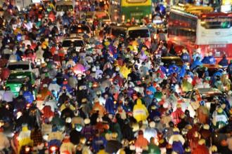 Rừng người di chuyển khó khăn trên đường trong cơn mưa chiều tối 26-8. Ảnh: Hữu Khoa