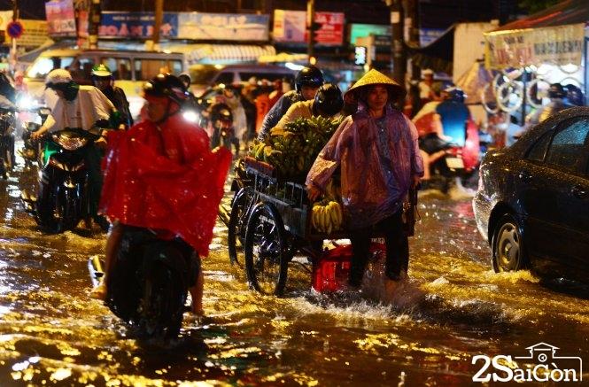 Một phụ nữ kéo xe chở chuối dưới cơn mưa. Ảnh: Duyên Phan
