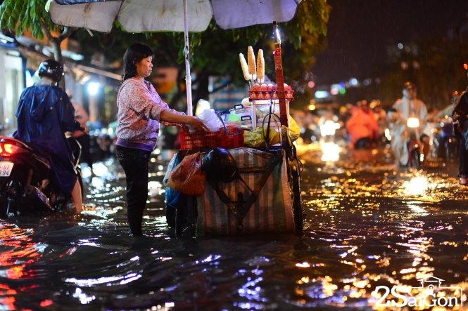 Một chị bán đồ ăn vặt chịu cảnh ngập trên đường Phan Xích Long, Q.Phú Nhuận, TP.HCM tối 26-8. Ảnh: QUANG ĐỊNH