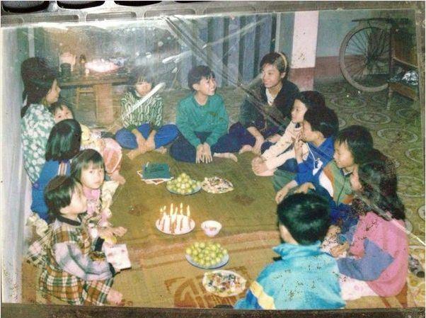 """Tụ tập ăn uống cùng bạn bè hồi ngày xưa thì trông thế này đây. Cũng có """"bàn tiệc"""" và hoa đấy, nhưng quây quần, ngồi trên…sàn nhà và nhạc thì mở từ băng cát-sét nhé!"""
