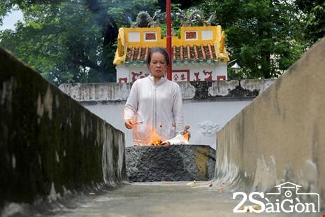 Người dân đốt giấy vàng bạc cúng tại ngôi mộ.