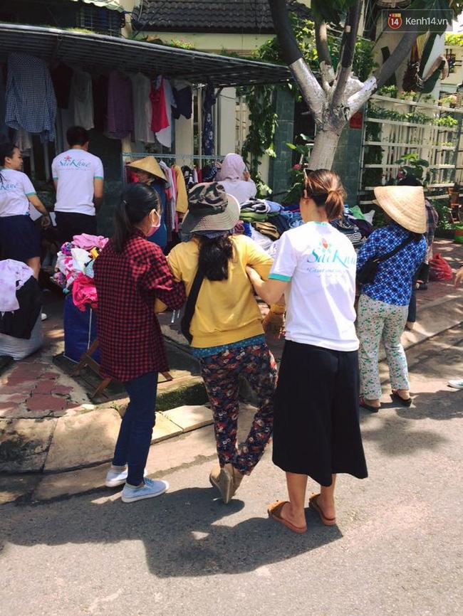 Các tình nguyện viên dìu chị bán vé số bị khuyết tật vào gian hàng.