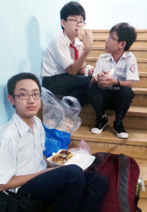Tranh thủ ăn cơm hộp sau giờ tan trường, chờ học thêm - Ảnh: Minh Luân