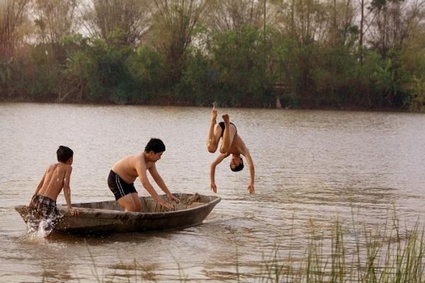 rẻ con tha hồ đùa nghich, vùng vẫy trong làn nước đỏ nặng phù sa -  Ảnh: Tiểu Hổ