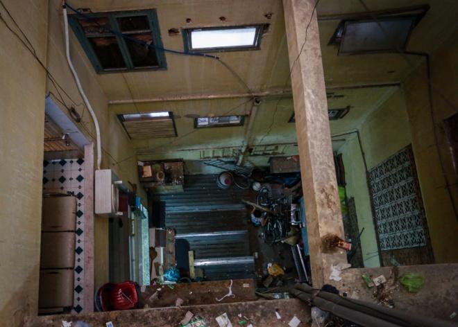 """Một hộ dân sửa lại những tấm tôn để tránh dột trần nhà. """"Do chung cư xây dựng lâu năm, một số hạng mục công trình xuống cấp nên cứ trời mưa, một số phòng của chung cư lại bị dột"""", bà Hương, một người dân đang thuê ở chung cư, cho biết."""