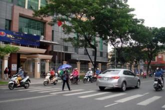 Chiếc dù xanh viền tím của một nữ sinh Trường ĐH KHXH&NV từ cổng trường ra lúc gần 9g sáng 4-11 - Ảnh: M.C.