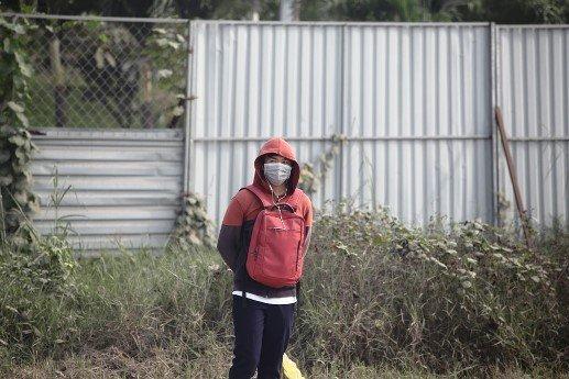 Nam sinh viên đứng chờ xe buýt trên đường Xa lộ Hà Nội phải bịt kín mặt, mũi...