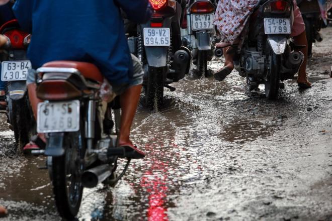"""""""Trước giờ ở đây ít kẹt lắm, giờ kẹt xe như cơm bữa, chưa kể cứ mưa xuống, nước đọng thành vũng, bốc mùi hôi thối vì cống không thoát nước được"""", ông Hiền nói."""