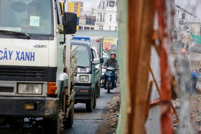 """Một người đi xe máy luồn lách giữa hàng rào công trình và ôtô trên đường Nguyễn Kiệm, quận Gò Vấp. Theo chị Nguyễn Thị Nhị, người bán tạp hóa ven đường, khu vực này chưa xảy ra tai nạn giao thông do """"lô cốt"""" nhưng người dân vẫn sợ hãi khi đi đường. """"Bà con ở đây rất mong công trình sớm hoàn thành để con đường sạch sẽ, đi lại an toàn"""", chị Nhị chia sẻ."""