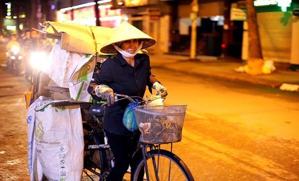 Bà Hoa gồng mình với chiếc xe ve chai trong đêm khuya. ẢNH: TRUNG DUNG.