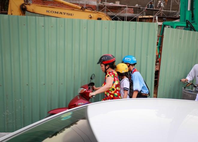 """Một người mẹ chở con phải nép vào hàng rào công trình để tránh ôtô trên đường Phan Văn Trị, đoạn tới cầu Hang Trong, quận Gò Vấp. Theo người dân, đoạn đường này vốn đã nhỏ hẹp, từ cuối tháng 10 mọc lên """"lô cốt"""" khiến tình trạng kẹt xe, va chạm xe xảy ra thường xuyên."""