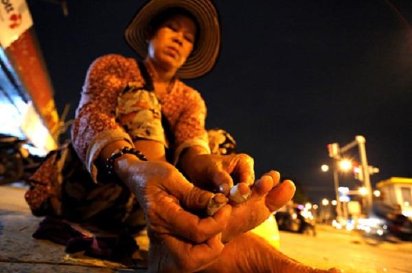 Bà Tính phải băng lại những ngón chân rướm máu sau một ngày đi bộ bán vé số