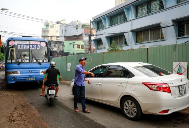 """Dãy """"lô cốt"""" mọc trên đường Phú Hữu, phường 14, quận 5 khiến con đường vốn là cửa ngõ của các loại xe buýt vào bến xe Chợ Lớn càng trở nên chật hẹp. Khi có hai ôtô đi ngược chiều, phụ xe phải nhảy xuống hướng dẫn tài xế lùi lại rồi đi tiếp."""