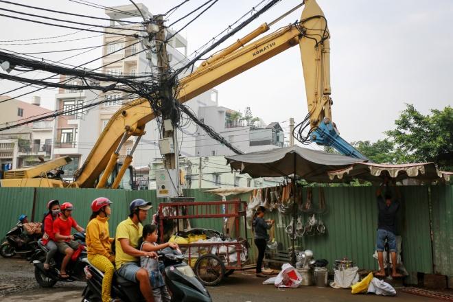 """Tương tự, sự xuất hiện của dãy """"lô cốt"""" trước cổng chợ Kim Biên, quận 5 khiến nhiều tiểu thương tại đây than trời vì lối đi lại và buôn bán chật hẹp hơn. Một số người tận dụng hàng rào công trình để bán hàng, bất chấp mối đe dọa từ những cần cẩu, trụ điện lơ lửng trong công trình đang thi công."""
