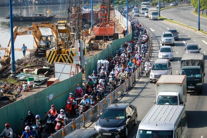 Hàng rào thi công kéo dài trên đường Võ Văn Kiệt, phía dưới cầu Nguyễn Văn Cừ (quận 1 và 5) khiến mật độ giao thông tại đây luôn đông đúc.