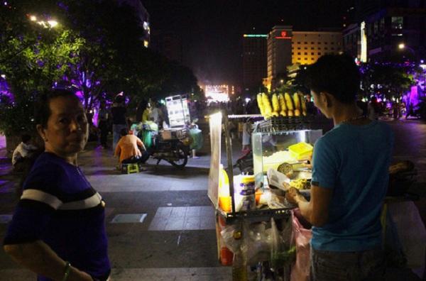 Một người phụ nữ mua bắp xào bên trong khuôn viên phố đi bộ, xa xa là nhiều xe hàng rong khác cũng nhộn nhịp không kém. Tiếng rao hàng, giành giật khách hàng, kẻ mua người bán vang lên huyên náo cả góc phố.