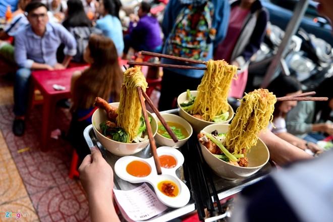 Mì bay có nguồn gốc từ Singapore nhưng thực chất đó là mì lạnh của Nhật. Những sợi mì ramen to dai được đặt khéo léo trên đôi đũa bay mang đến cảm giác như đang lơ lửng trong không trung. Ảnh: Tùng Tin.